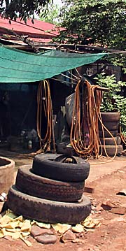 'Old Tyres and a Hose in a Workshop in Cambodia' by Asienreisender